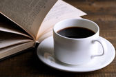 Cup of hot coffee with book on wooden background — Stock Photo