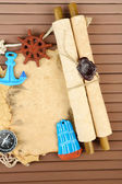 Old paper with sea accessories, isolated on wooden background — Photo