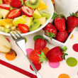 Stock Photo: Useful fruit salad of fresh fruits and berries in bowl on napkin on wooden table close-up