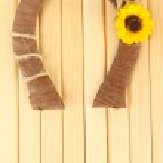 Decorative horseshoe of straw with sunflower, on wooden background — Stock Photo