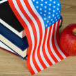 Composition of American flag, books and apple on wooden table background — Stock Photo