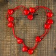 Stock Photo: Heart-shaped beads on string on wooden background