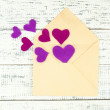 Beautiful old envelope with decorative hearts on wooden background — Stock Photo