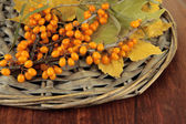 Branch of sea buckthorn and yellow leaves on wicker stand on wooden background — Stock Photo