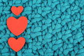 Hearts made of felt on green knitted background — Stock Photo