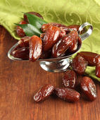 Dried dates in metal dish with napkin on wooden background — Stock Photo