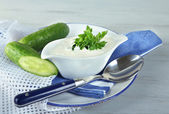 Cucumber yogurt in sauceboat, on color napkin, oncolor wooden background — ストック写真