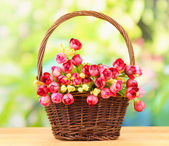 Bouquet of beautiful artificial flowers basket, on wooden table — Stock Photo