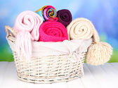 Warm knitted scarves in basket on wooden table on natural background — Stock Photo