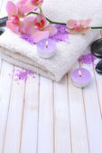 Still life with beautiful blooming orchid flower, towel and bowl with sea salt, on color wooden background — Stock Photo