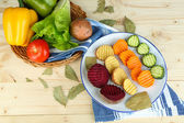 Beautiful sliced vegetables, on plate, on wooden background — ストック写真