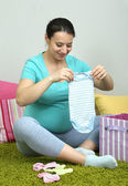 Young pregnant woman sitting on carpet and folding baby wear on wall background — Stock Photo
