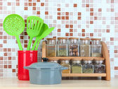 Set of spices, tableware and kitchen utensils in kitchen on table on mosaic tiles background — Stock Photo