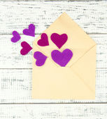 Beautiful old envelope with decorative hearts on wooden background — Stok fotoğraf