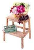 Cestino di vimini con fiori e frutti, su piccola scala in legno, isolato su bianco — Foto Stock