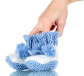 Hand with crocheted booties for baby, isolated on white — Stock Photo