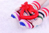 Female hands in mittens with heart on snow background — Stock Photo
