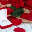 Stock Photo: Ring surrounded by roses and petals on wooden table close-up