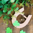 Stock Photo: Horseshoe and clover on wooden table close-up