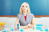 Chemistry teacher sitting at table on blackboard background — Stock Photo
