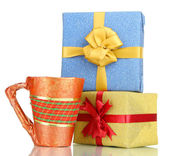 Cup packed in gift paper with gifts isolated on white — Stock Photo