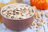 Pumpkin seeds in bowl with pumpkin on wooden background — Stock Photo