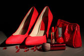 Beautiful red female shoes and cosmetics, on black background — Stock Photo