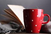 本および格子縞灰色の背景にテーブルの上で熱いお茶のカップ — ストック写真