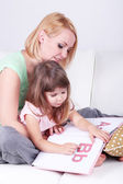 Pretty little girl reading book with mother on sofa on gray background — Stock Photo