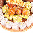 Tasty oriental sweets on wicker tray, isolated on white — Stock Photo #39546891