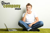 Young man relaxing on carpet with laptop, on gray wall background — Stock Photo
