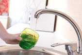 Hand holding glass of water poured from kitchen faucet — Stock Photo