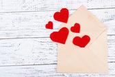 красивый старый конверт с декоративными сердечками на деревянных фоне — Стоковое фото