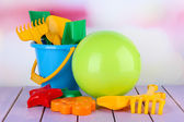 Bright ball and sandbox toys on table on bright background — Стоковое фото