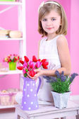 Little girl sitting on small ladder with flowers on pink background — Stock Photo