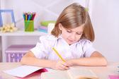 部屋に机に座っている小さな女の子 — ストック写真
