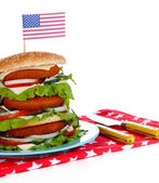 Composition with huge burger on color plate and USA flag, isolated on white — Stock Photo