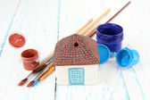 Hand made ceramic house and color paints on wooden table — Stock Photo