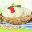 Tasty crispbread with berries in wicker basket, on green table — Stock Photo #39580631