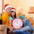 Young couple with boxes in new home celebrating New Years — Stock Photo #39583043