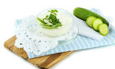 Cucumber yogurt in bowl, on wooden board, isolated on white — Stock Photo