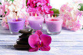 Beautiful colorful candles, spa stones and flowers,on color wooden background — Stock Photo