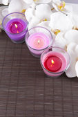 Composition with beautiful colorful candles, sea salt and orchid flowers, on bamboo mat, on light background — Stock Photo