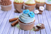 Tasty cupcakes with butter cream, on color wooden background — Stock Photo