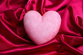 Decorative red heart, on color fabric background — Stock Photo