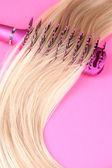Cabello largo y rubio con cepillo sobre fondo rosa — Foto de Stock