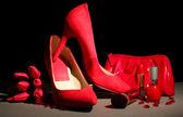 Belle rosse scarpe femminile e cosmetici, su sfondo nero — Foto Stock