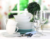 Clean dishes on table on window background — Stock Photo