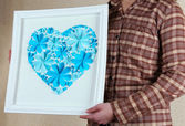 Woman holding beautiful handmade picture with heart from paper flowers — Stock Photo
