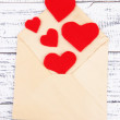 Beautiful old envelope with decorative hearts on wooden background — Stock Photo #39599597